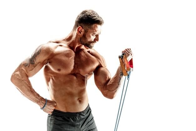 Handsome muscular strong man doing pulling exercise and working hard.