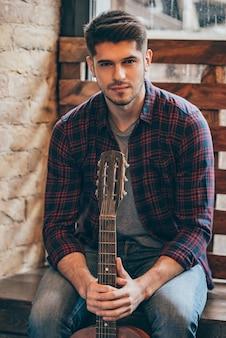 ハンサムなミュージシャン。ギターを持って窓辺に座ってカメラを見ているハンサムな若い男