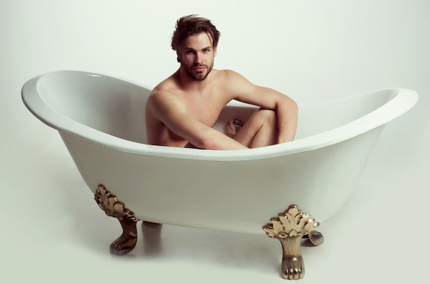 Handsome naked man sitting in bathtub sporty man takes a bath isolated on white