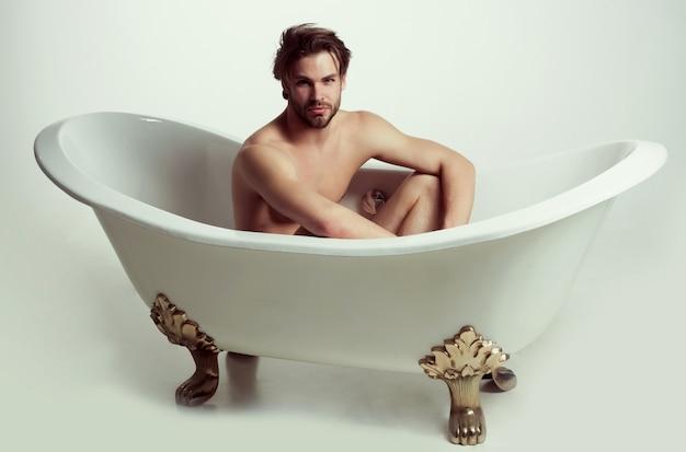 バスタブに座っているハンサムな裸の男スポーティーな男は白で隔離風呂に入る