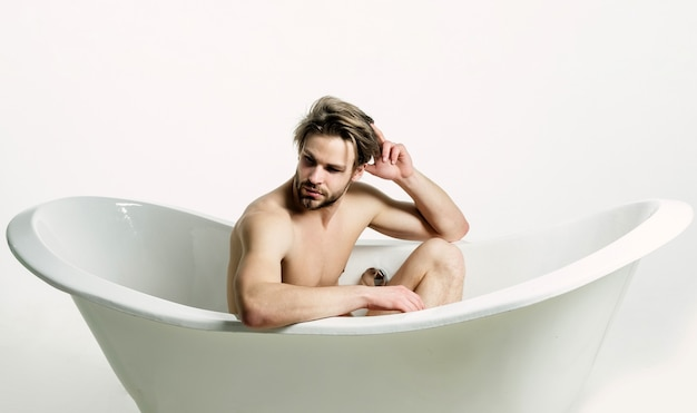 욕조에 앉아 벌거 벗은 근육질의 몸통을 가진 잘 생긴 벌거 벗은 남자 스포티 한 남자는 흰색에 고립 된 목욕을 걸립니다