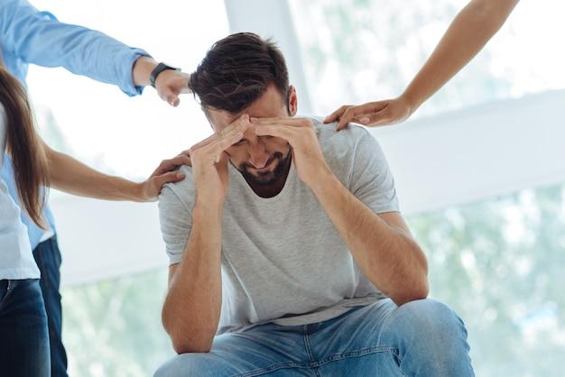 ハンサムな素敵なストレスのたまった男が前かがみになり、うつ病を抱えている間彼の問題について考えています