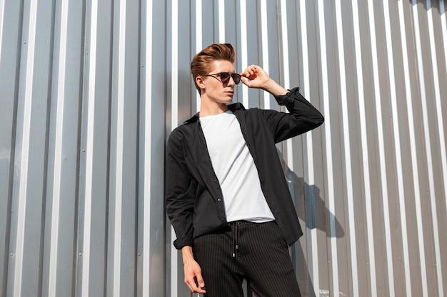 화창한 날에 금속 실버 벽 근처 포즈 줄무늬 바지에 티셔츠에 우아한 검은 셔츠에 선글라스에 유행 헤어 스타일으로 잘 생긴 좋은 젊은 남자 소식통. 현대 남자 패션 모델.