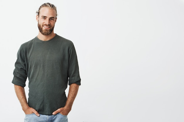 Handsome nordic man with beard and stylish hairstyle in grey shirt and jeans smiling, keeps hands in pockets.
