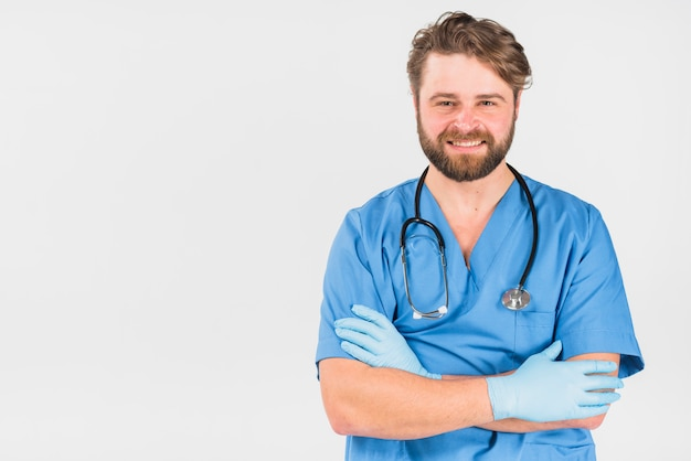 Handsome nurse male smiling and crossing hands