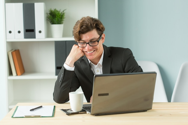 Handsome office man laughing at workplace