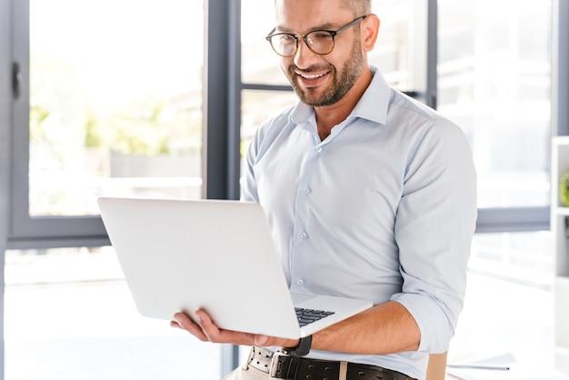 Красивый офисный мужчина в белой рубашке, выражающий успех, держа серебряный ноутбук во время работы в бизнес-центре