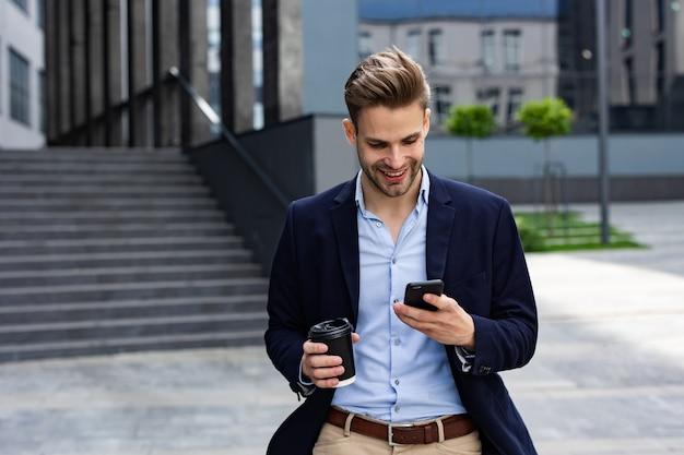 스마트폰 들고 웃 고 잘생긴 회사원입니다. 휴대폰 앱을 사용하고, 문자 메시지를 보내고, 인터넷을 검색하고, 스마트폰을 보고 있는 행복한 청년. 비즈니스 센터 근처에서 커피 브레이크.