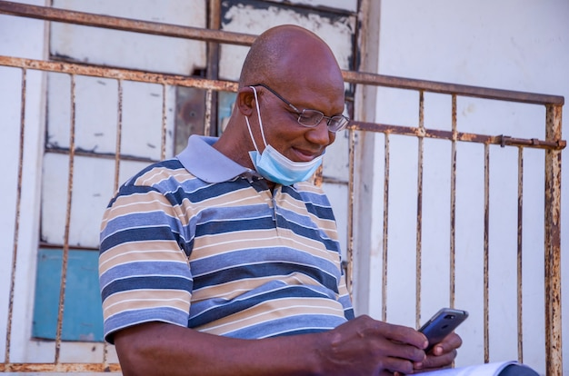 Красивый старый африканец в маске для лица во время работы со своим телефоном.