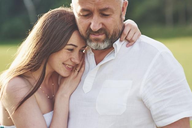 Красивый старик и красивая молодая девушка обнимаются, дочь и ее старый папа проводят время вместе на открытом воздухе