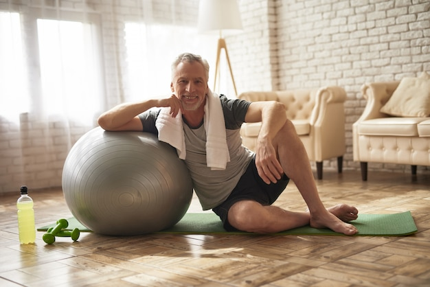 Handsome old man does pilates workout at home.