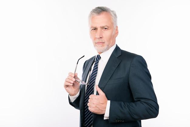 Красивый старик в деловом костюме держит очки, показывая пальцем вверх