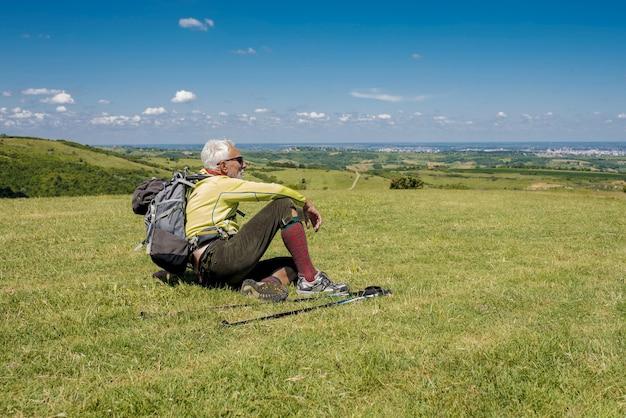 Красивый старик сидит на лугу и расслабляется после похода