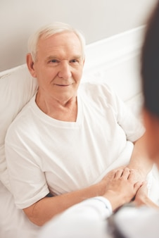 Handsome old patient is talking to his doctor