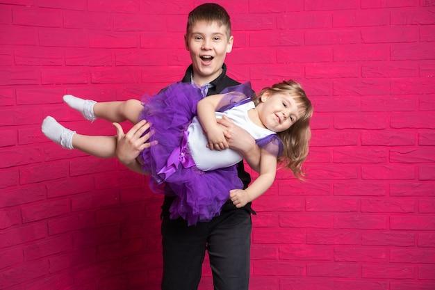Красивый подросток старшего брата, держа на руках свою милую сестренку на розовом фоне.