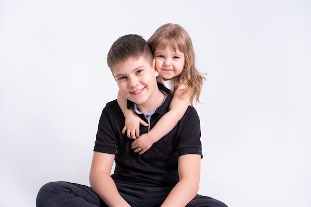 Красивый подросток старшего брата, обнимая свою милую сестренку на белом фоне.