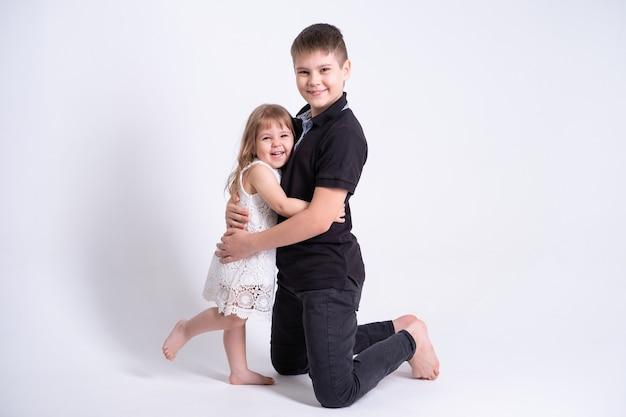 Красивый старший брат подросток обнимает свою симпатичную младшую сестру на белом