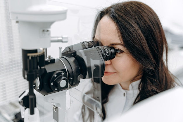 Красивый офтальмолог осматривает пациента с помощью современного оборудования.