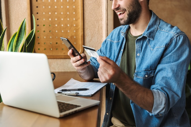 Handsome optimistic man wearing denim shirt holding cellphone and credit card with laptop while working in cafe indoors