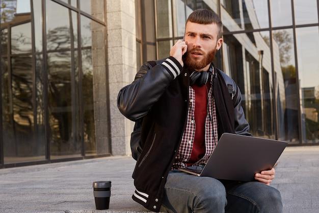 Красивый возмущенный рыжебородый молодой парень сидит на улице, кладет ноутбук на колени, разговаривает по телефону с другом, который опаздывает на полчаса.