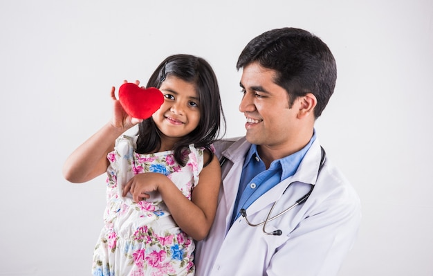 흰색 배경 위에 절연 빨간색 박제 심장 장난감을 들고 아기 여자 환자를 들고 잘 생긴 소아과 남성 의사