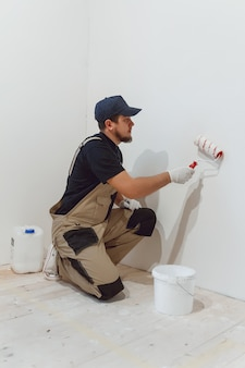 Handsome painter with paint roller in empty room paints the wall