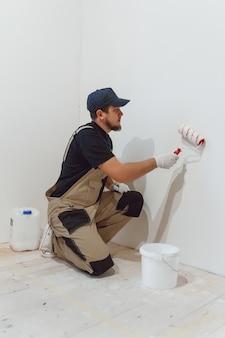 空の部屋にペイントローラーを持つハンサムな画家が壁をペイントします