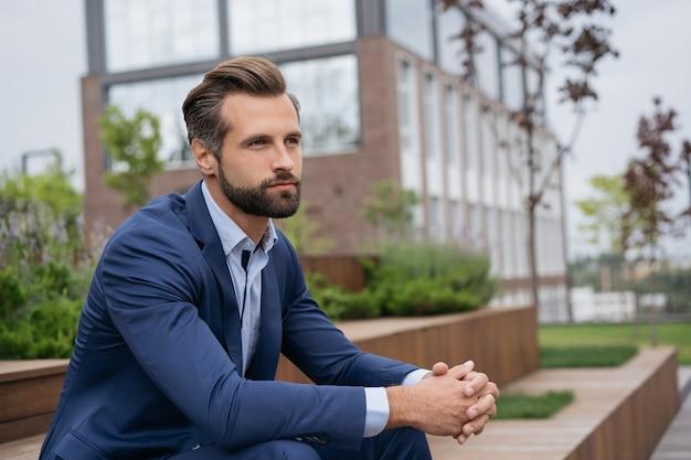 Красивый задумчивый бизнесмен, планирующий проект, расслабляющий в парке цифровая концепция детоксикации