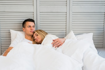 Handsome pensive man hugging young woman lying on bed