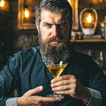 Красивый задумчивый мужчина держит стакан виски. вечеринка с напитками