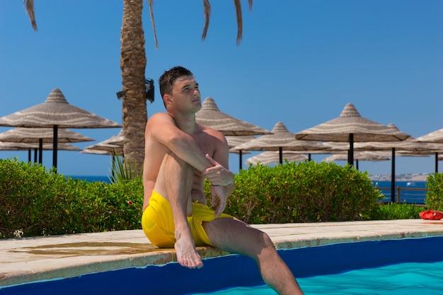 화창한 여름날 호텔 수영장 가장자리에 앉아 있는 잘생긴 남자