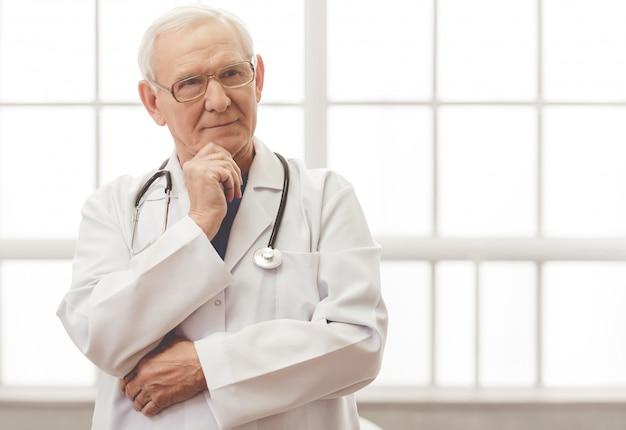 Handsome pensive old doctor in eyeglasses is looking away