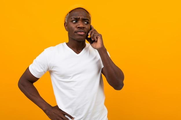 노란색 스튜디오에 전화로 얘기하는 흰색 티셔츠에 잘 생긴 잠겨있는 심각한 미국 사람