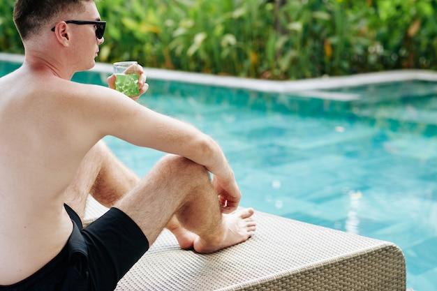 Красивый задумчивый молодой человек сидит у бассейна, пьет холодный напиток и смотрит на воду