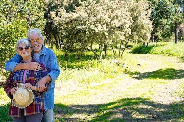 Красивые люди обнимаются в лесу, на зеленом лугу и деревьях. старшая счастливая пара, наслаждающаяся здоровым образом жизни