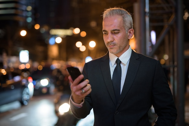 Handsome persian businessman wearing suit in city at night