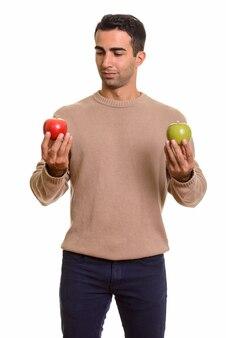 건강 한 녹색 및 빨강 사과 들고 잘 생긴 페르시아 남자