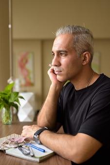 회색 머리를 생각하고 도서관에서 창 밖을보고 잘 생긴 페르시아 남자