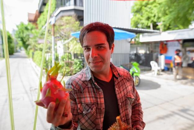 ストリートショップで果物を買い物するハンサムなペルシャの観光客の男
