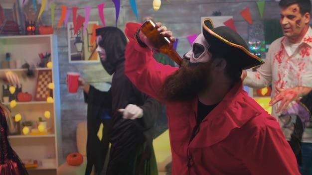 Красивый пират с топором пьет пиво, празднует хэллоуин со своими страшными друзьями, танцующими в украшенной комнате.