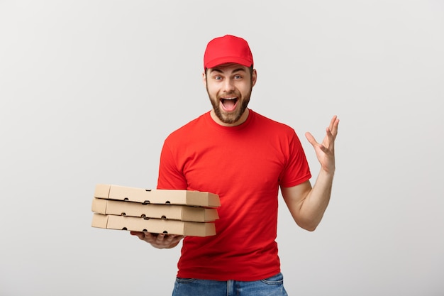 Handsome pizza delivery man courier in red uniform with cap holding pizza boxes.