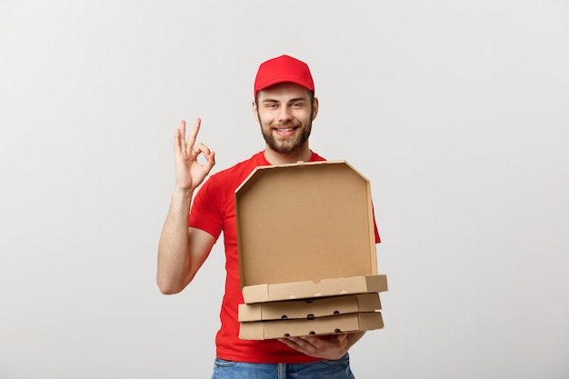 Handsome pizza delivery man making ok sign isolated over grey background.