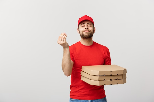 Handsome pizza delivery man showing delicious expression over grey background