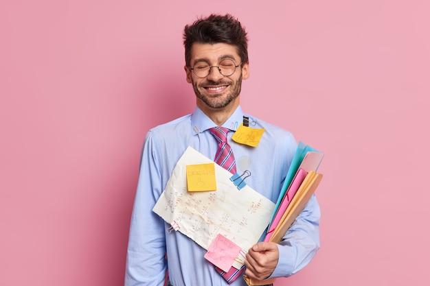 ハンサムで喜んで陽気な未経験のビジネスマンの笑顔は、ステッカーで覆われたドキュメントのフォルダーを喜んで保持しますフォーマルなシャツを着て、ネクタイは交渉や同僚との会議の準備をします