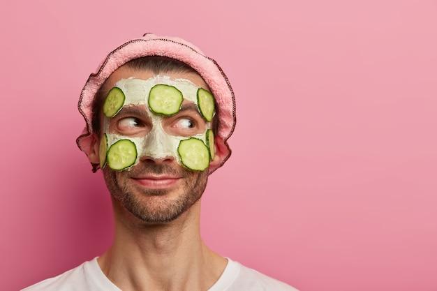 Un bell'uomo contento riceve un trattamento viso, applica una maschera all'argilla con fette di cetrioli, gode di procedure di bellezza, ha setole