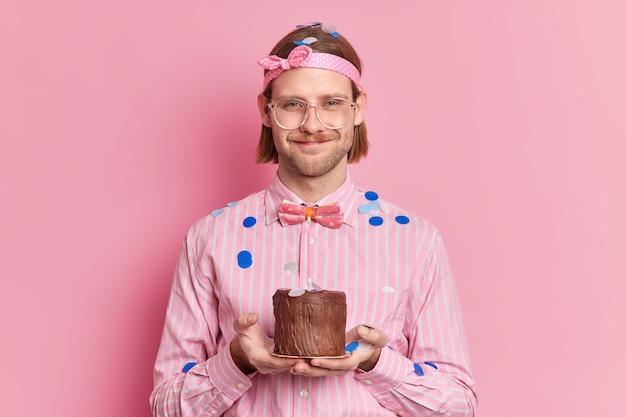 ハンサムな喜んでいる男は、ピンクの壁に隔離された紙吹雪に囲まれたお祝いの服を着て燃えるろうそくと小さなチョコレートケーキを保持しています