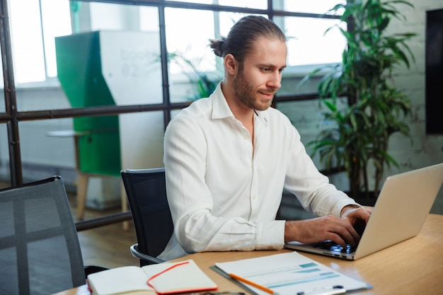 Красивый довольный мужчина с щетиной работает с ноутбуком, сидя за столом в современном офисе