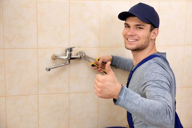 Handsome plumber fixing faucet in bathroom
