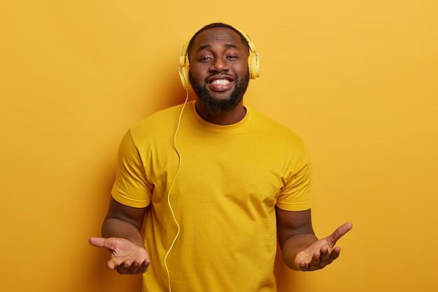 Bel ragazzo paffuto dalla pelle scura ha un umore perfetto con musica fresca, gode di un buon suono in cuffia
