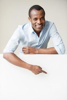 Красивый указывая копией пространства. веселый африканский мужчина в синей рубашке, опираясь на копировальное пространство и указывая на него, стоя на сером фоне